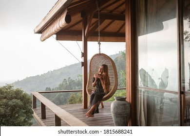 Tourist woman swing on wicker rattan hang chair in the jungle, nature mountains view, hold in hands cup of tea/coffee