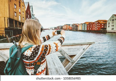 Tourist woman taking photo by smartphone sightseeing in Norway Lifestyle vacations outdoor scandinavian colorful houses landmarks Trondheim city  architecture
