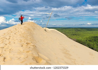Tourist woman taking photo with a smartphone at the top of the Pilat dune, the highest of Europe, Bassin d'Arcachon, Aquitaine, France