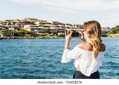 Tourist woman taking photos of the sea and small italian city on her cell phone, selective focus