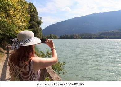 Tourist woman taking picture of Castle Castel Toblino with smartphone in Italy