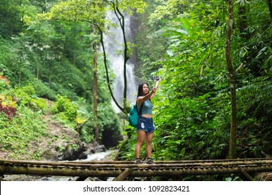 Tourist woman taking a selfie on a bamboo bridge near the Red Coral waterfall in the Munduk jungle, Bali, Indonesia