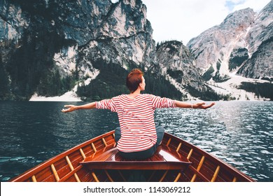 Tourist woman in traditional wooden rowing boat on italian alpine Braies Lake. Girl enjoying stunning view of Lago di Braies in Dolomites, South Tyrol, Italy, Europe. Beauty of nature background.
