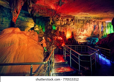 Tourist woman in underground cave Sataplia with colorful illumination in Kutaisi, Georgia