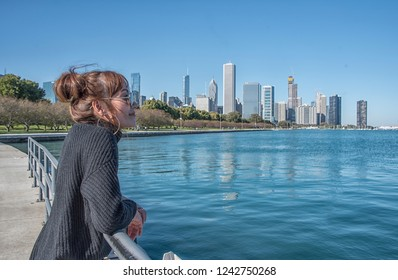 Tourist woman visit architecture of Chicago she walking Lincoln Park near lake. Chicago, Illinois, USA.