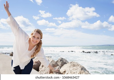 Tourist woman visiting coastal beach destination on holiday, playful stretching arms looking smiling, joyful fun outdoors. Female energy against blue sunny sky, leisure recreation lifestyle, wellness.