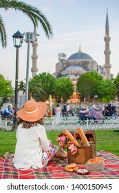 Tourist woman waiting for iftar in Sultanahmet Square. Blue Mosque is seem on background. Picnic in Istanbul. Young woman enjoying summertime in Istanbul, Turkey.