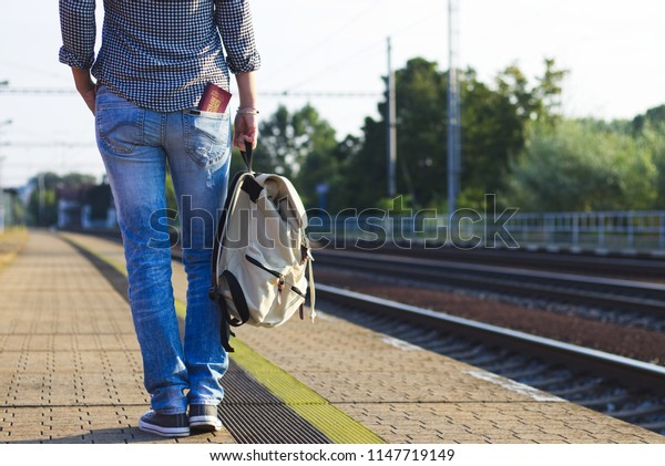 Tourist woman waiting for international train on railway station. Woman with backpack and passport in pocket travelling on Europe.