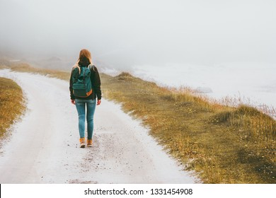 Tourist woman walking alone outdoor Travel Lifestyle wanderlust concept foggy nature adventure active vacations