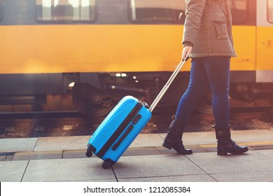 Tourist woman walking at railway station. Travel by train. Girl dragging blue luggage suitcase. Journey concept. Lifestyle, travelling, vacation. Autumn, winter travel. Woman with blue suitcase