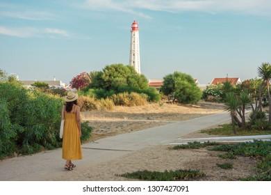 Tourist woman walking under the lighthouse of Farol Island in Formosa Estuary, Algarve, Portugal.