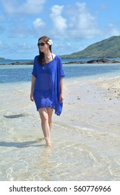 Tourist woman walks along a remote beach of an Island in Fiji. Travel holiday vacation concept. Real people copy space
