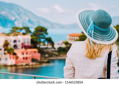 Tourist woman wear blue sunhat and white clothes admire view of colorful tranquil village Assos on sunny day. Stylish female visiting Kefalonia enjoying summer time on Greece travel vacation
