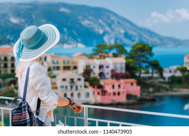 Tourist woman wearing blue sunhat and white clothes enjoying view of colorful tranquil village Assos on sunny day. Stylish female visiting Kefalonia in summer time on Greece travel vacation