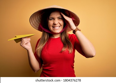 Tourist woman wearing traditional asian rice paddy straw hat holding paper plane for a trip stressed with hand on head, shocked with shame and surprise face, angry and frustrated. Fear and upset