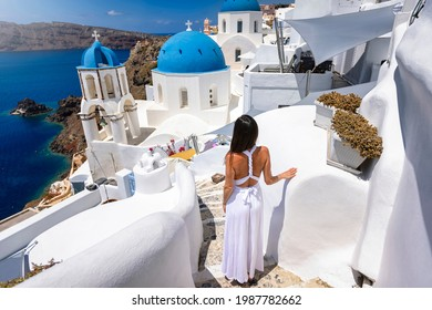 A tourist woman in a white dress explores the whitewashed houses of the little village Oia on the edge of the volcanic caldera in Santorini island, Greece, during summer time