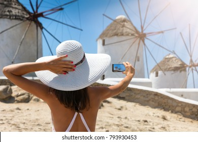 Tourist woman with white hat takes a picture of the famous windmills of Mykonos, Greece