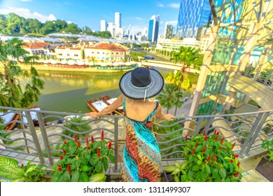 Tourist woman with wide hat looking panorama from terrace over Clarke Quay and Riverside area in Singapore, Southeast Asia.Cruise on Singapore River in sunny day and skyscrapers downtown on background