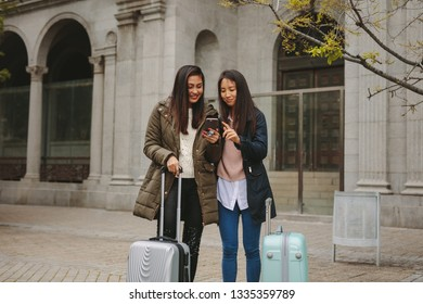 Tourist women standing in street with luggage bags looking for directions in cell phone. Two smiling asian tourists looking at mobile phone.