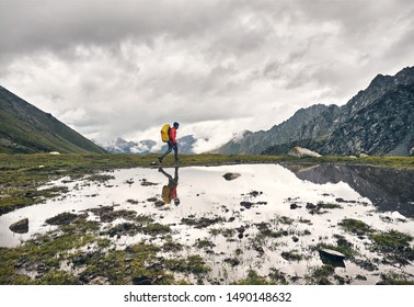 Tourist with yellow backpack is walking near lake with his reflection at green valley in Karakol national park, Kyrgyzstan