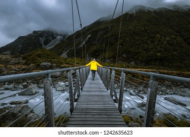 tourist with yellow jacket walking cross suspension bridge over Hooker river at Hooker Valley Track in Aoraki Mountain Cook National Park in south island of New zealand during cloudy day