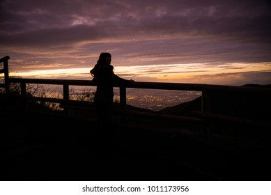 Tourist young girl admiring Naples at sunset from mount Vesuvius. Beautiful landmark above the city, Italy