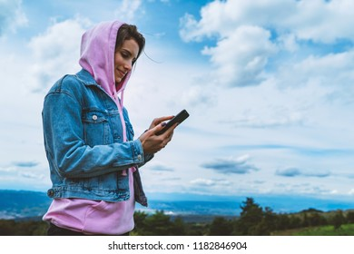 tourist young girl on background blue sky using mobile smartphone, person holding in female hands gadget technology, texting finger message on screen content online wifi internet lifestyle concept