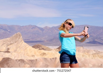 Tourist young girl taking pictures photo selfie in Death Valley desert landscape of Zabriskie Point in Death Valley National Park, California, USA. Young girl on travel in United States.