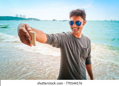 Tourist young handsome Indian man wear sunglasses selfie at sea beach on vacation