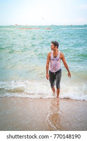 Tourist young handsome Indian man enjoy with sea wave at sea beach on vacation
