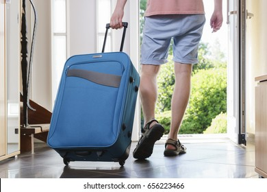 Tourist young man in T-shirt, shorts and sandals with blue vacation bag exits through the front door.