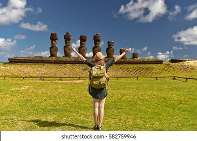 Tourist young woman with bag on Anakena beach with Moai statues, Easter island, Chile