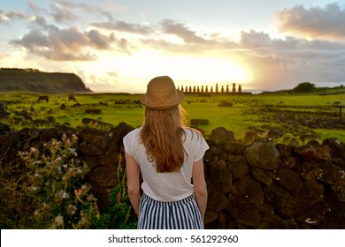 Tourist young woman girl in hat  looking on sunrise and Ahu Tongariki on Easter Island, Chile