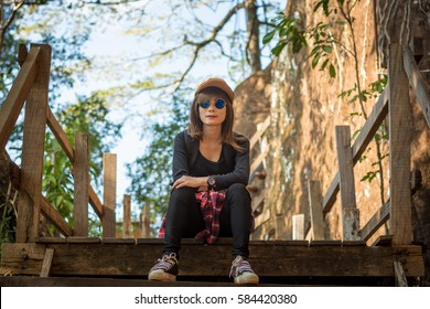 Tourist young woman wearing hat enjoying sitting on the stairs mountain.