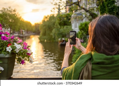 a tourist young women  in Amsterdam take pictures at a beautiful sunset on a bridge
