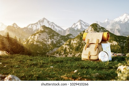 Touristic backpack with map and compass on grass field at mountain in summer day. Travel and vacation concept