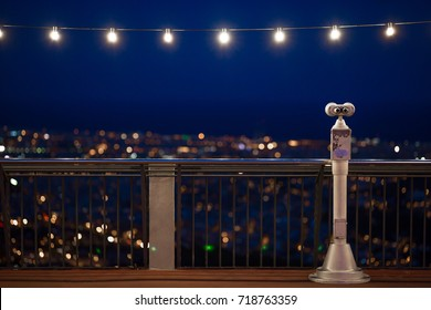 Touristic binocular with the view on a night cityscape with lightning lamps above.