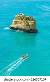 Touristic boat sailing on Algarve beautiful Atlantic coast and turwuoise waters.