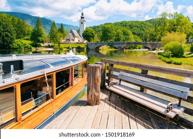 Touristic boat and wooden bench and Scenery at Church of St John Baptist on Bohinj Lake in Slovenia. Nature in Slovenija. View of blue sky with clouds. Beautiful landscape in summer.