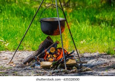 touristic cauldron on a tripod in a fire