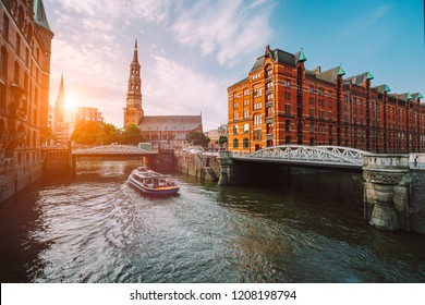 Touristic cruise boat on a channel with bridges in the old warehouse district Speicherstadt in Hamburg in golden hour sunset light, Germany
