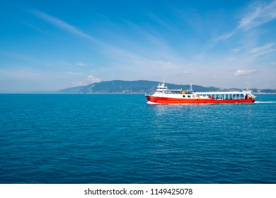 Touristic ferry cruising on the sea with cars and passengers. The ship close to shore and lonely on the sea.