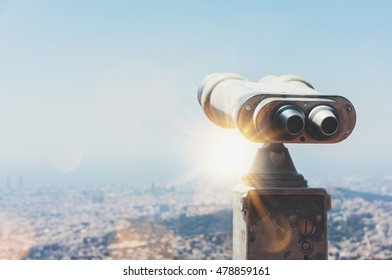 Touristic telescope look at the city Barcelona Spain, close up metal binoculars on background viewpoint overlooking the mountain, hipster coin operated in panorama observation blue sky, mockup flare