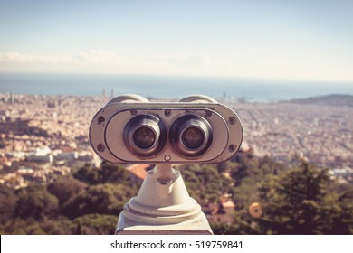 Touristic telescope look at the city Barcelona Spain, close up metal binoculars on background viewpoint overlooking the mountain, hipster coin operated in panorama observation blue sky