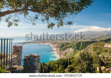 The touristic village Giardini Naxos, East Sicily, and snowy Mount Etna seen from a viewpoint of the roman theater in Taormina