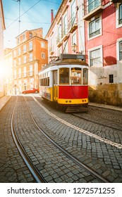 Touristic vintage red tram in a Lisbon street on sunny afternoon, narrow streets, cobblestones winding road, vacation in Lisbon.