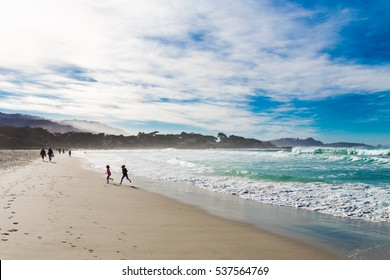 Tourist,local people,kids,family,having fun,walking,jogging,running,playing at the Carmel State beach,California with big blue sky and deep turquoise sea of Pacific Ocean