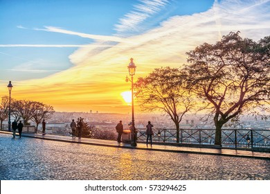 Tourists admire the panoramic view of Paris on the morning sunrise from the Montmartre hill.