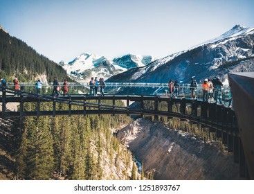 Tourists admiring the panorama while walking on the glass floor at Glacier Skywalk, Icefields Parkway, Alberta, Canada