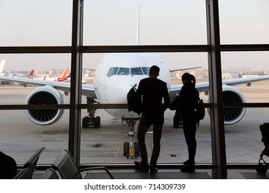 Tourists at the airport. Passengers looking the airplane. Silhouettes of people.